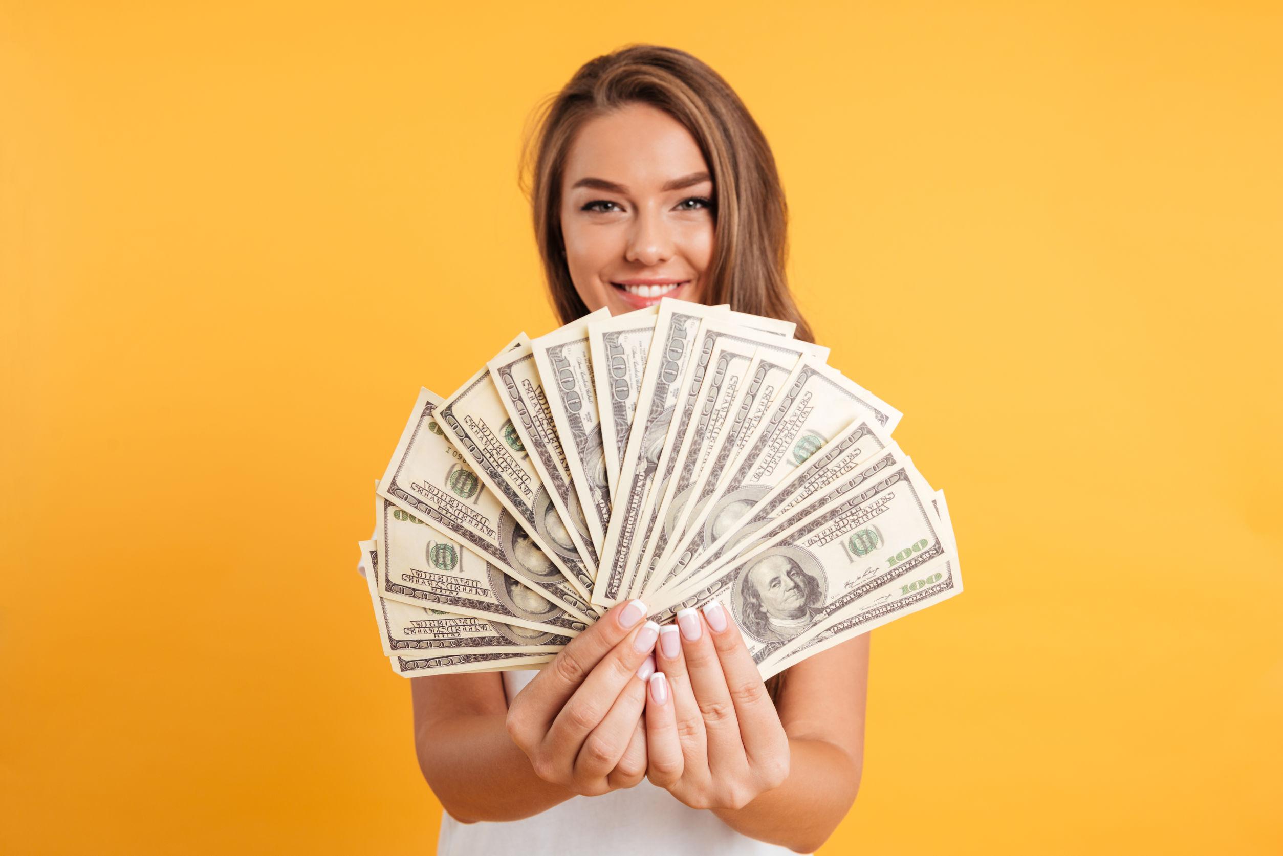 Mulher sorrindo e mostrando dinheiro para a tela