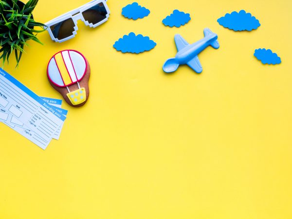 Sample of airplane ticket. Family trip with kid. Airplan, air balloon toys. Yellow background flat lay space for text.