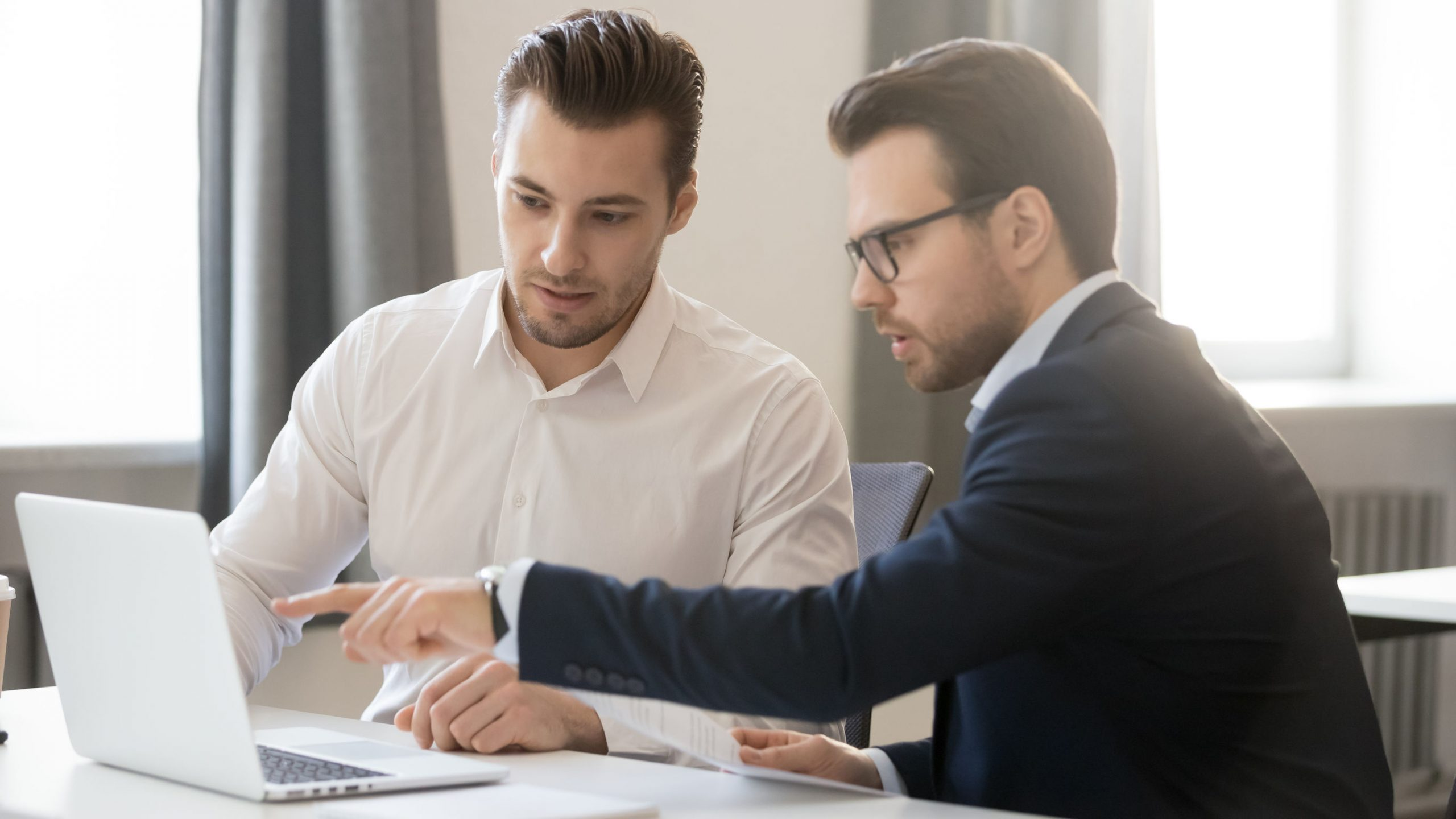 Dois homens na foto, um deles apontando para o computador e o outro olhando atentamente