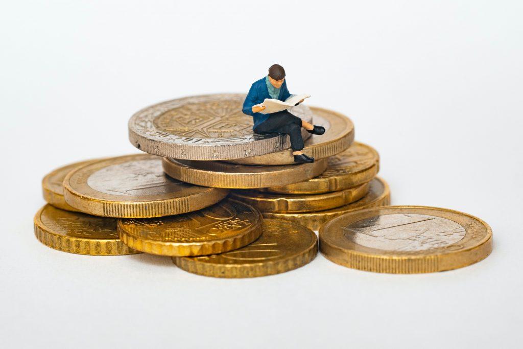 Boneco sentado em cima de moedas
