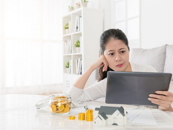 attractive elegant woman decided using personal saving money investing new house and looking at online estate information through mobile digital tablet pad feeling confused.