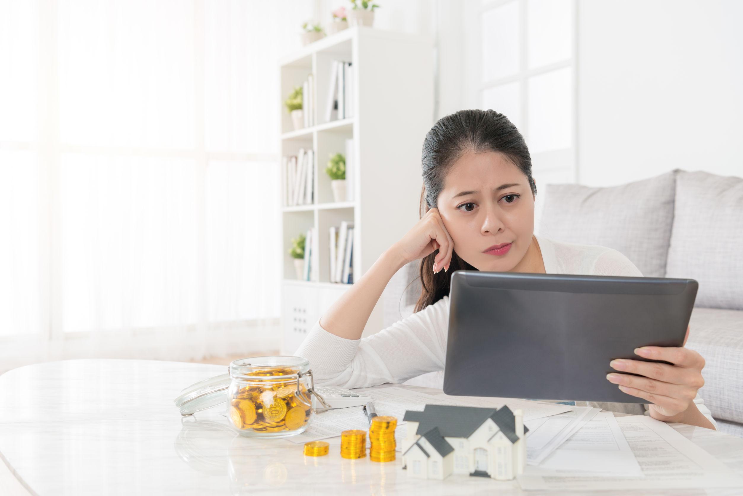 mulher olhando para o tablet pensando onde investir o dinheiro