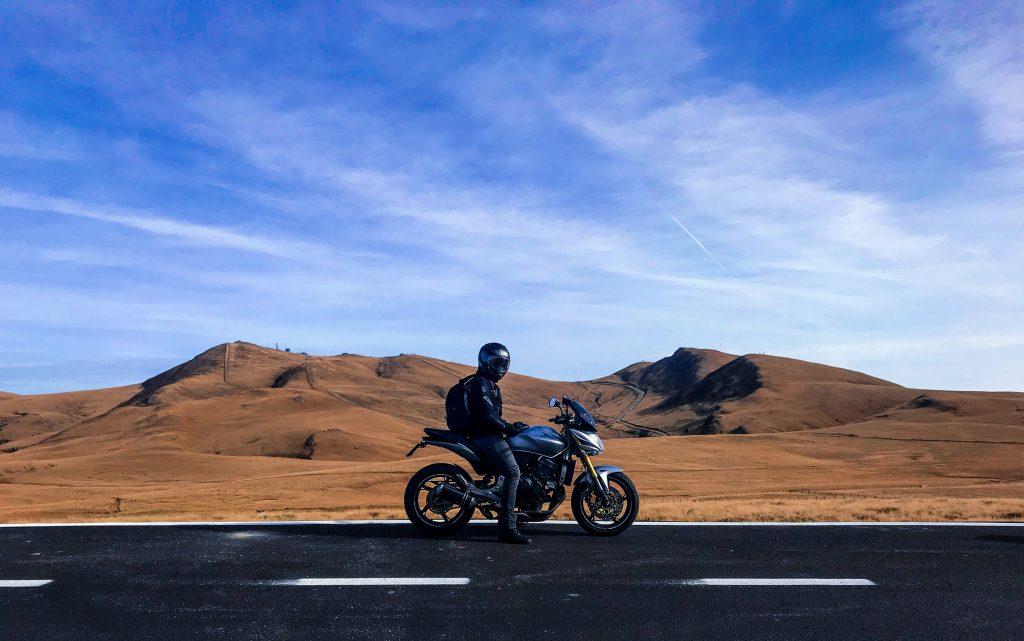 Foto de uma moto parada no meio da estrada com um deserto de fundo