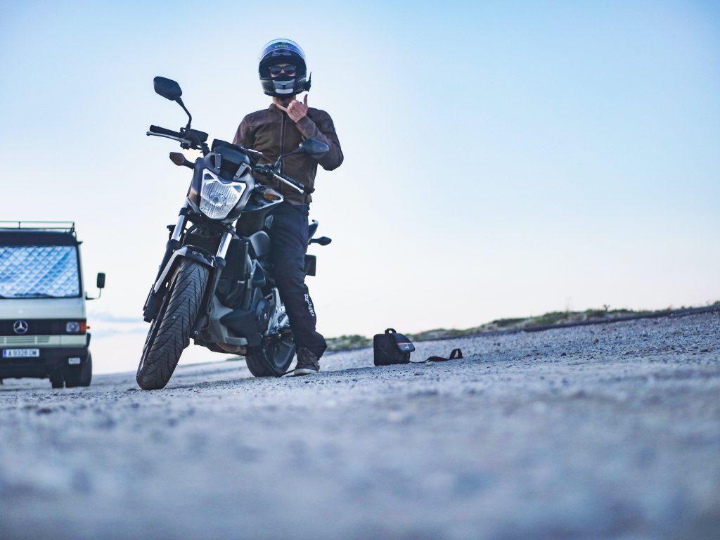 Foto de um Homem em cima de uma moto fazendo sinal de hang loose para a foto