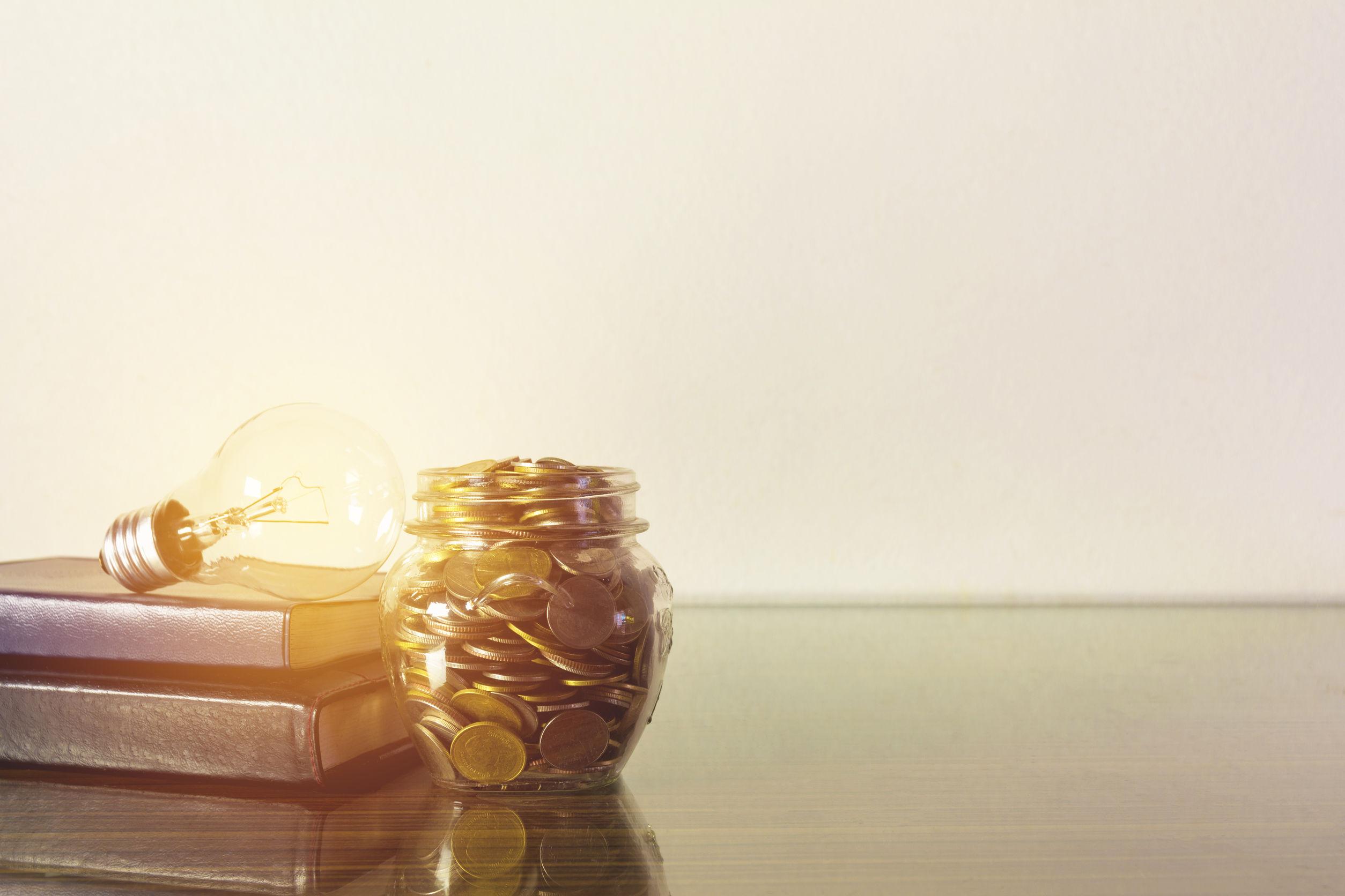 Dois livros no canto esquerdo com uma luz em cima dos livros iluminando a imagem em direção a um cofrinho cheio de moedas.