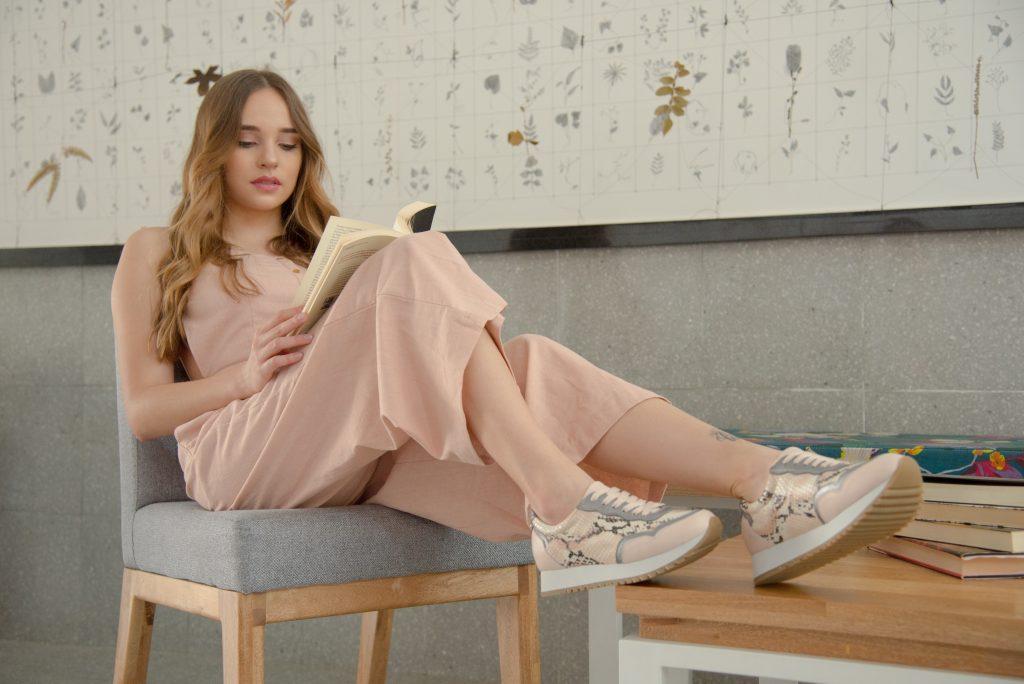 Foto mostra uma mulher sentada em uma cadeira lendo um livro