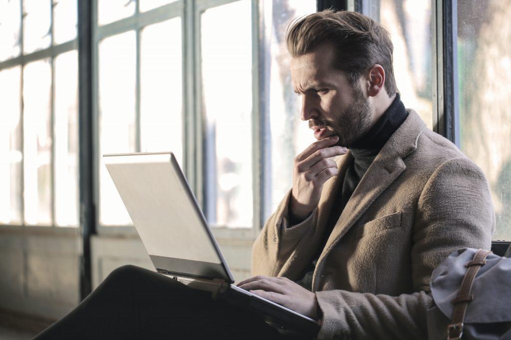 Homem pensativo com a mão no queixo olhando fixamente para o computador