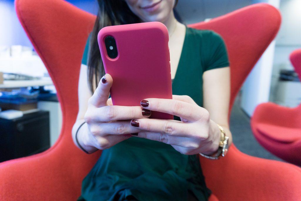 Mulher de blusa verde e unhas bordô segurando um celular rosa sorrindo para o que está olhando