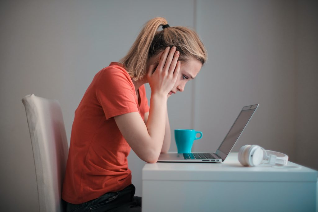 A foto mostra uma mulher segurando a cabeça com as duas mãos e olhando para o computador com tristeza