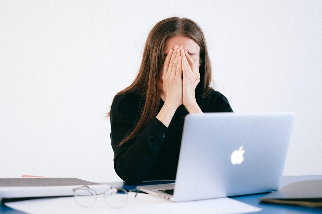 A foto mostra uma mulher em um ambiente de trabalho com as mãos tampando o rosto em sinal de tristeza
