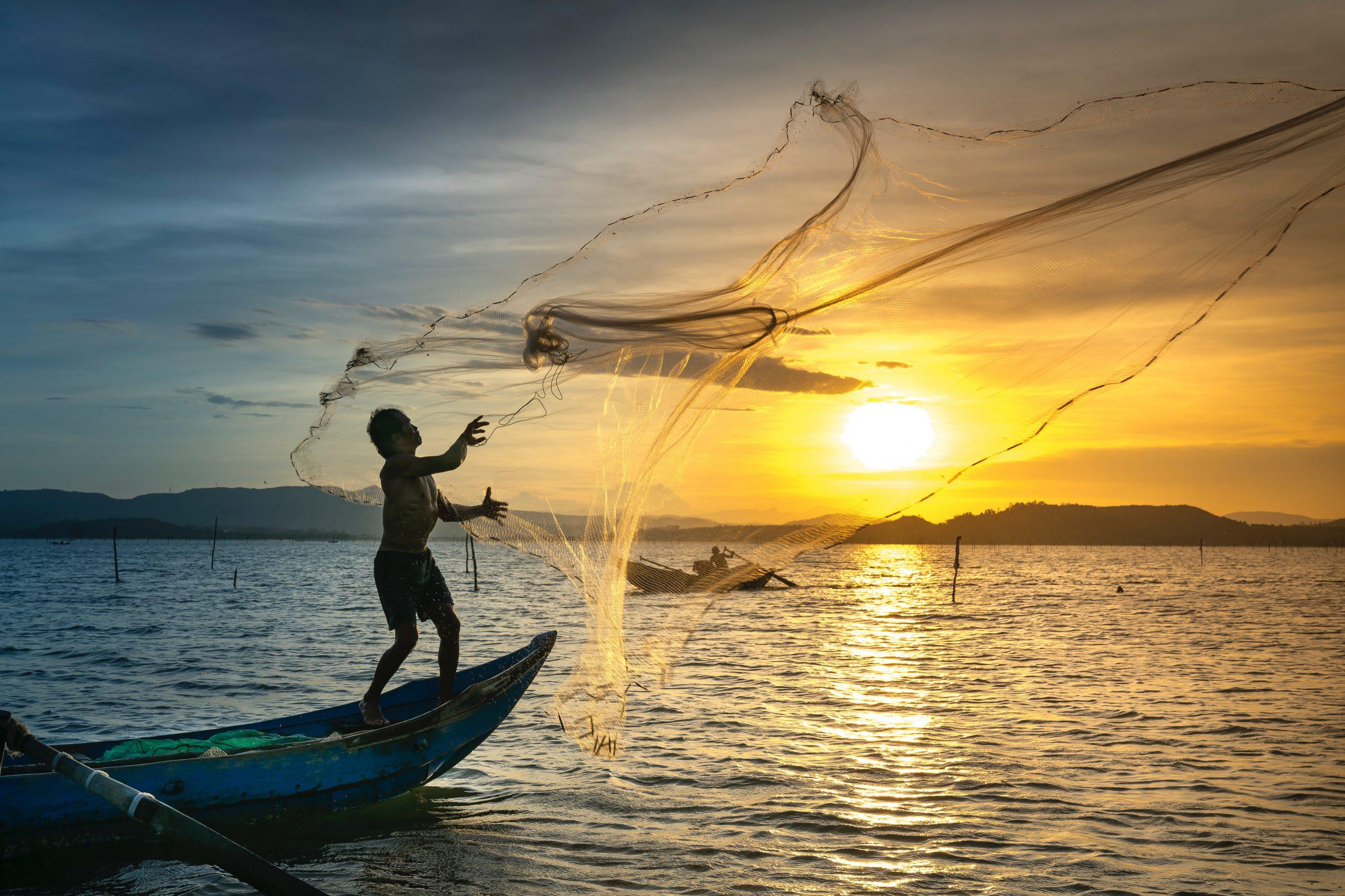 Homem em cima do barco jogando a rede de pesca no mar