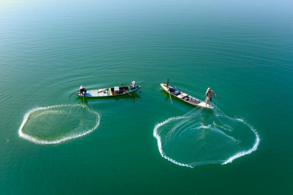 Foto de dois homens jogando redes ao mar, cada um em seu barco