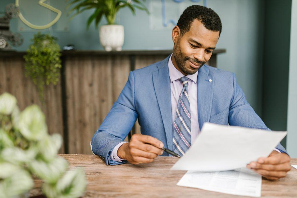 Foto de um homem olhando para um contrato com uma caneta na mão para assiná-lo