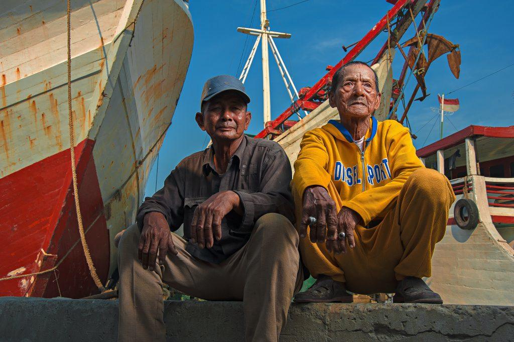 Foto de dois pescadores sentados em frente ao barco