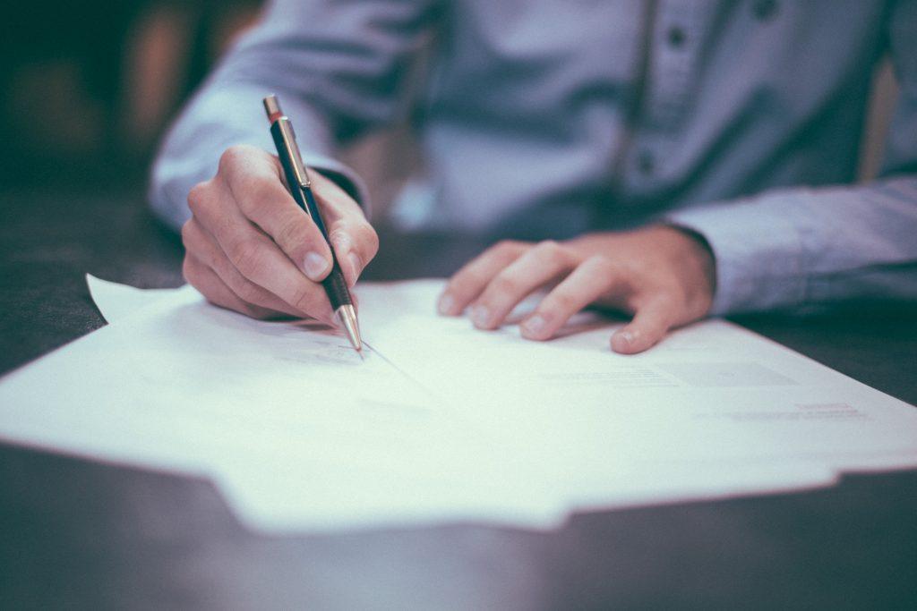 Foto em que aparece as mãos de um homem assinando um contrato