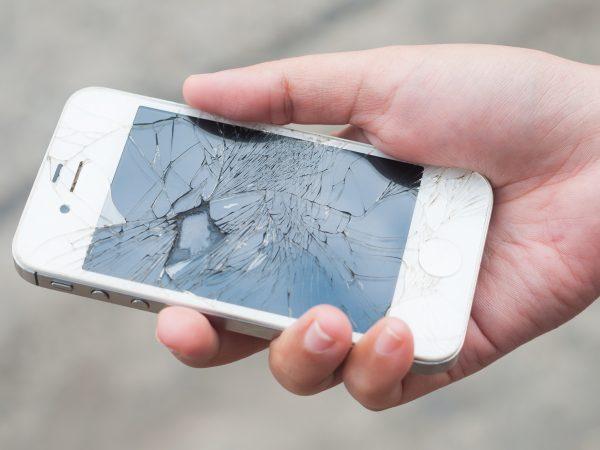 A foto mostra uma mão segurando um celular com a tela quebrada