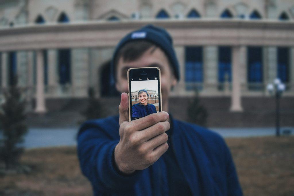 Garoto segura celular com a mão e bate selfie em frente à ponto turístico
