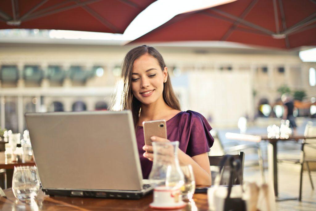 Mulher em uma cafeteria mexendo no celular