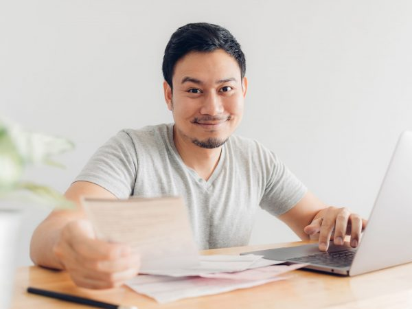 Happy Asian man has cleared the problems with billing and debts.