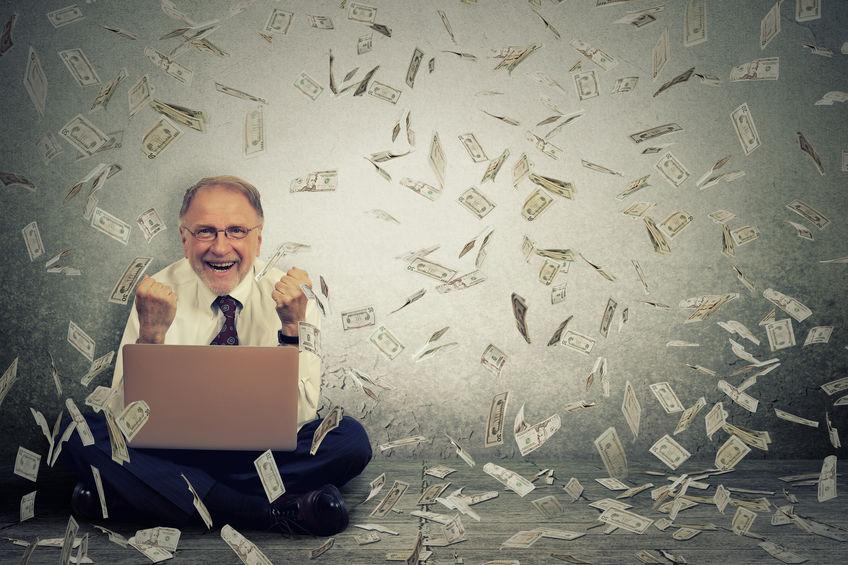 Homem sentados com um computador no colo e várias notas de dólar no colo dele