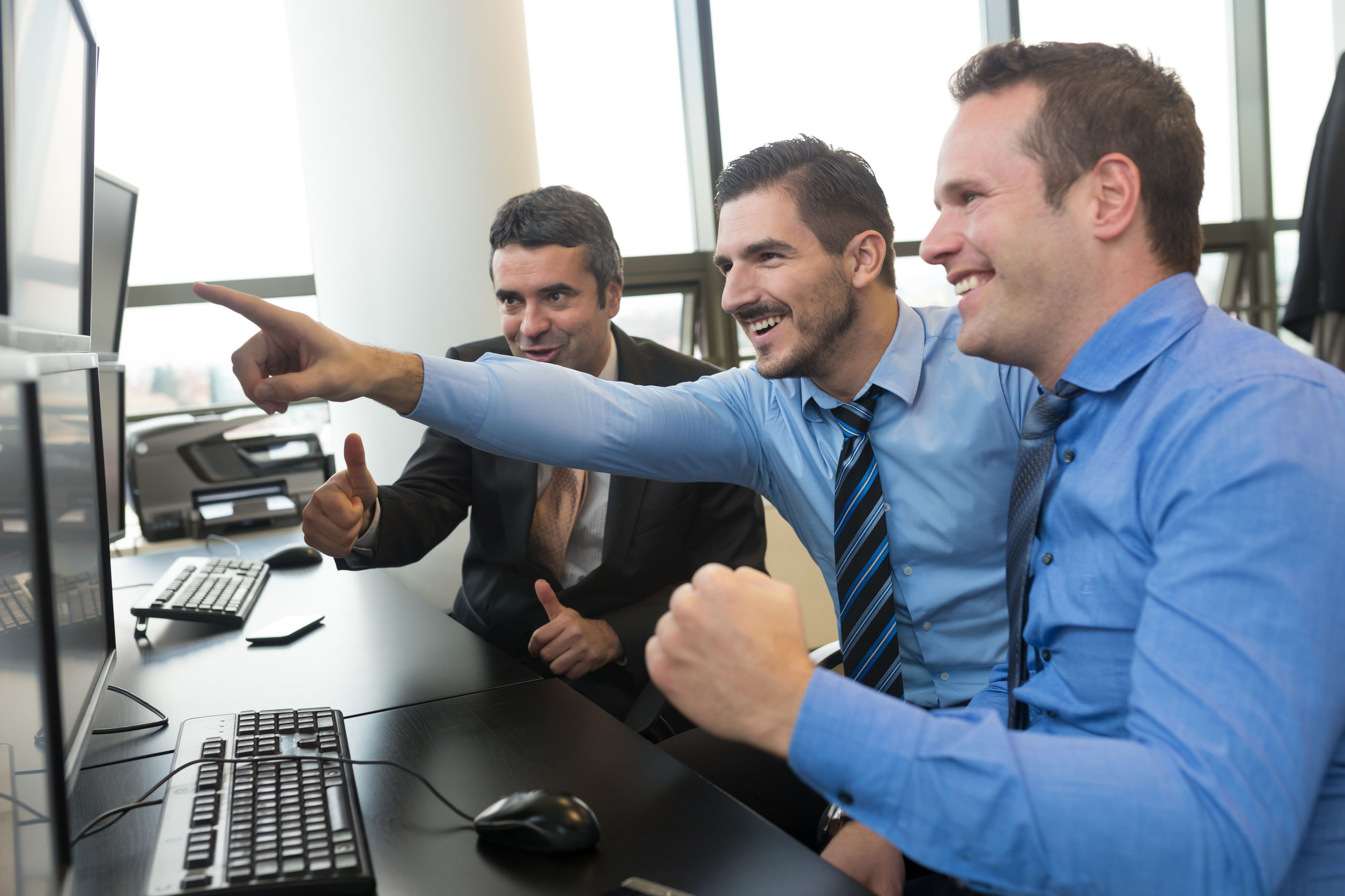 Três homens olhando e apontando para telas de computador com um sorriso no rosto