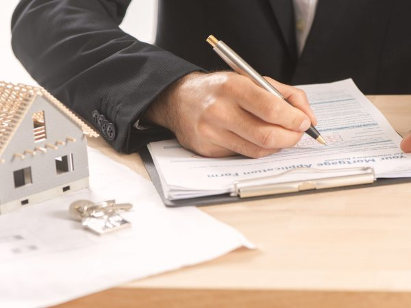 Businessman signing a mortgage  contract  of a sale for a new house