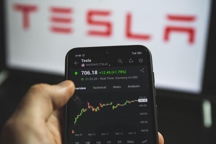 Mão segura o celular com o gráfico da Tesla em aberto