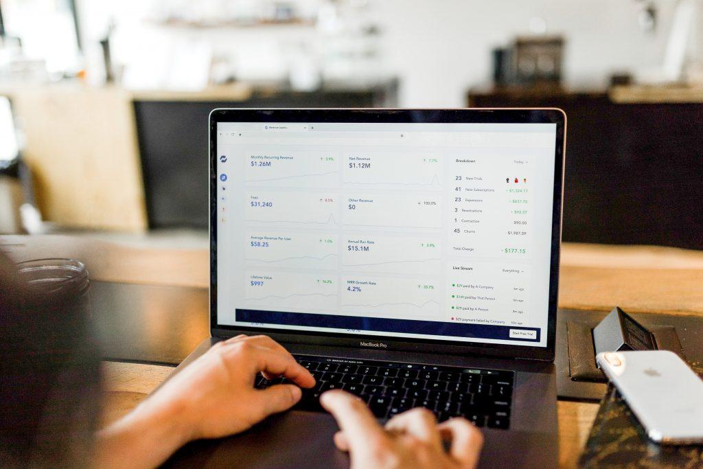 A foto mostra um homem em frente ao computador olhando para uma análise fundamentalista de uma empresa