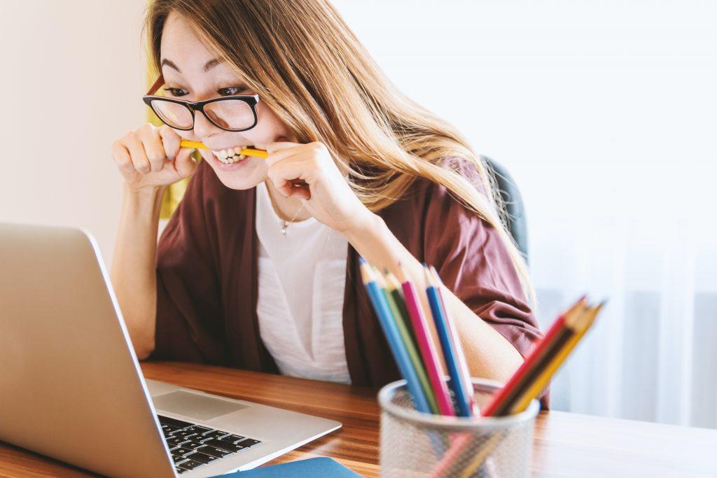 A foto mostra uma mulher em frente ao computador com o lápis na boca em sinal de apreensão