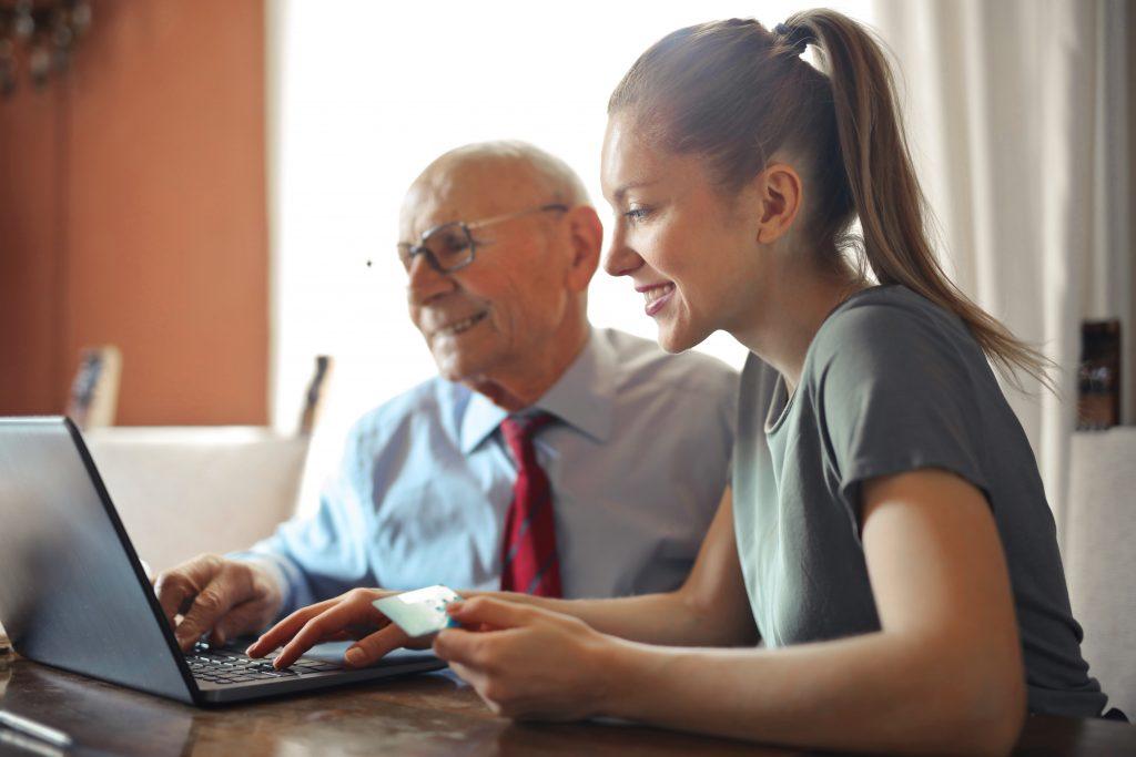 Mulher mais jovem ajudando um senhor idoso a realizar uma compra pelo computador