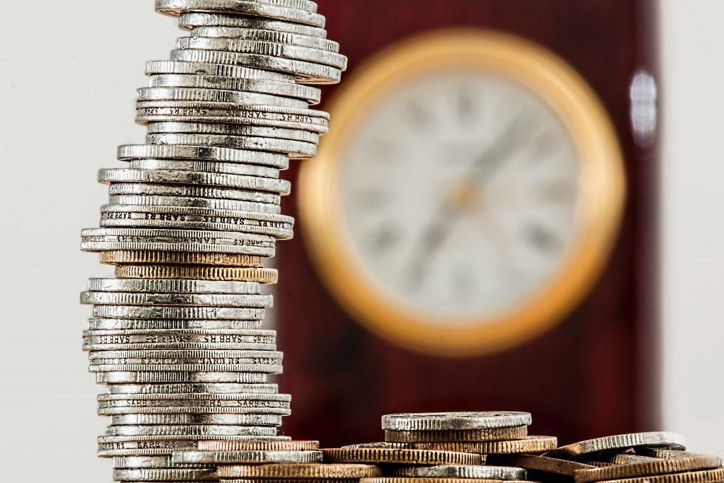 A foto mostra várias moedas empilhadas, com um relógio caracterizando o tempo de fundo