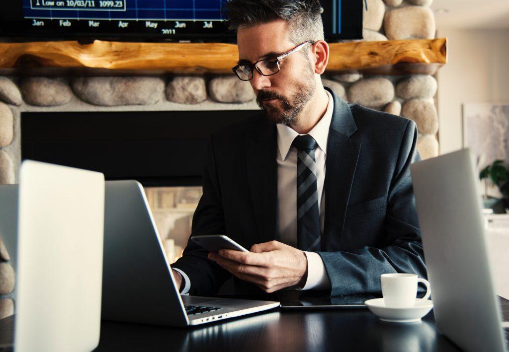 A foto mostra um Homem mexendo no celular e computador ao mesmo tempo provavelmente analisando suas finanças