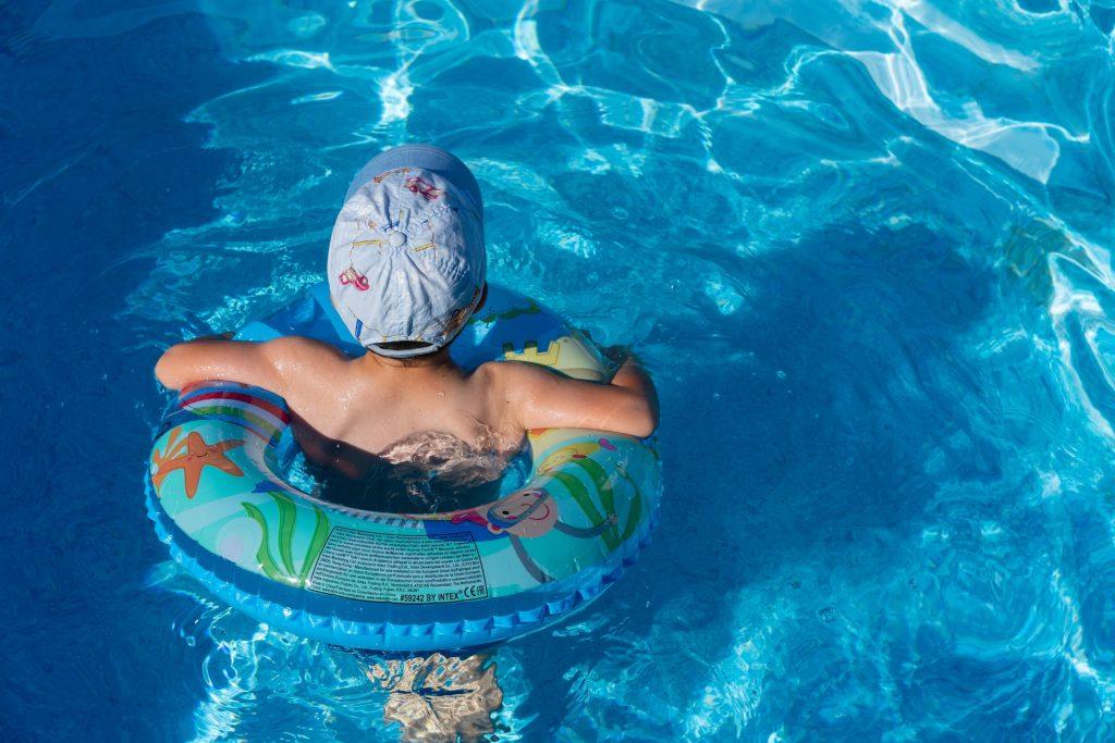 Niña en piscina usando flotador