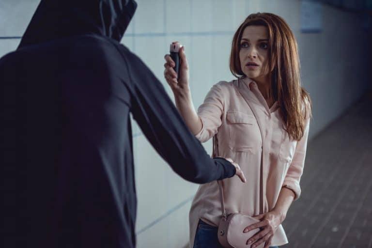 Una mujer siendo atracada y usando un spray de pimienta