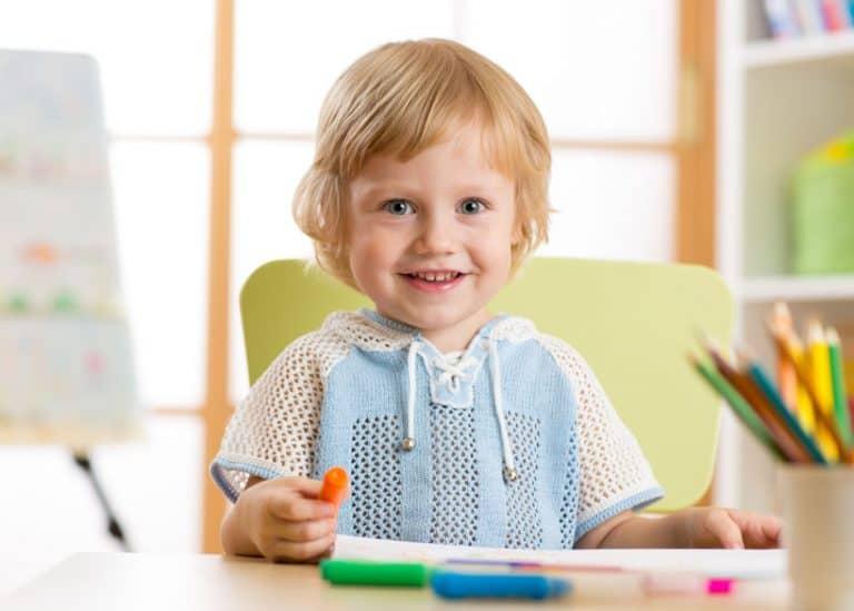 Niño sonriendo con color en la mano