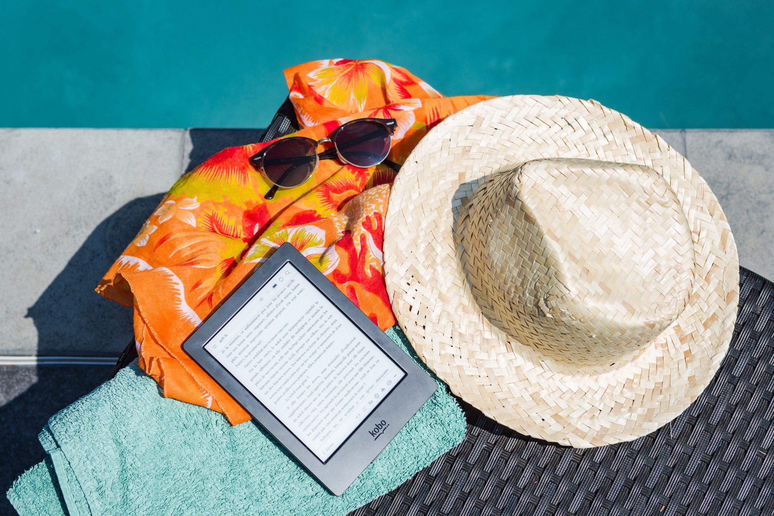 Tablet sobrero de playa, y lentes junto a piscina