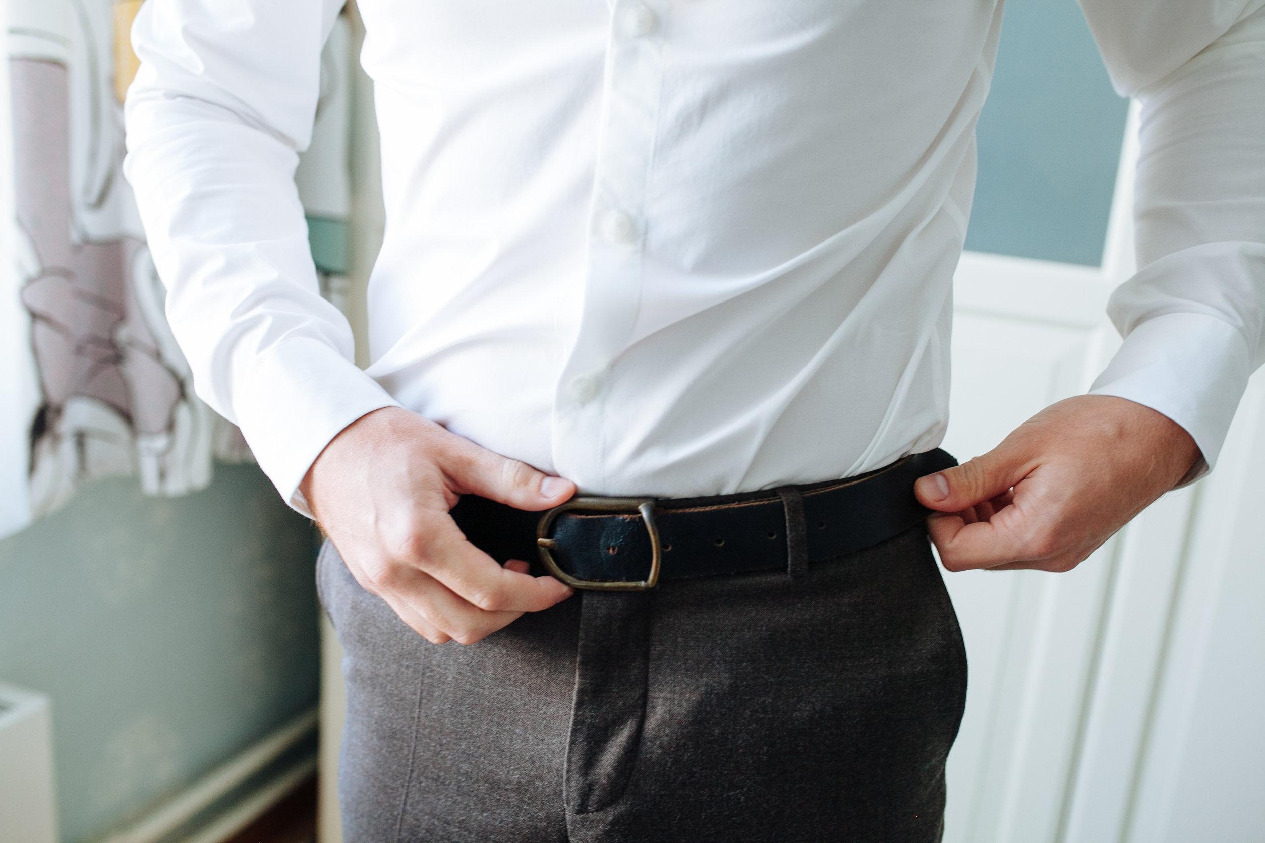O homem de calças castanhas e uma camisa branca prendeu um cinto de calças de couro preto.