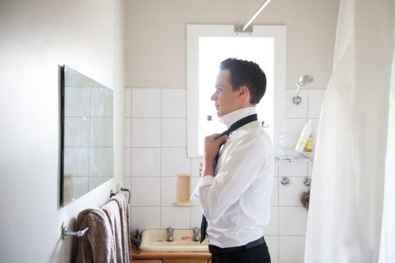 Hombre en el baño ajustándose la corbata
