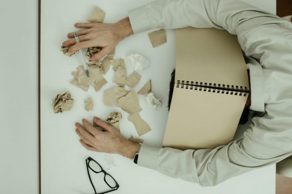 Persona en mesa con cuaderno de carton y tiras de papel
