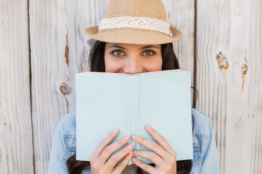 Mujer atractiva con libro en manos cubriéndose la mitad de la cara