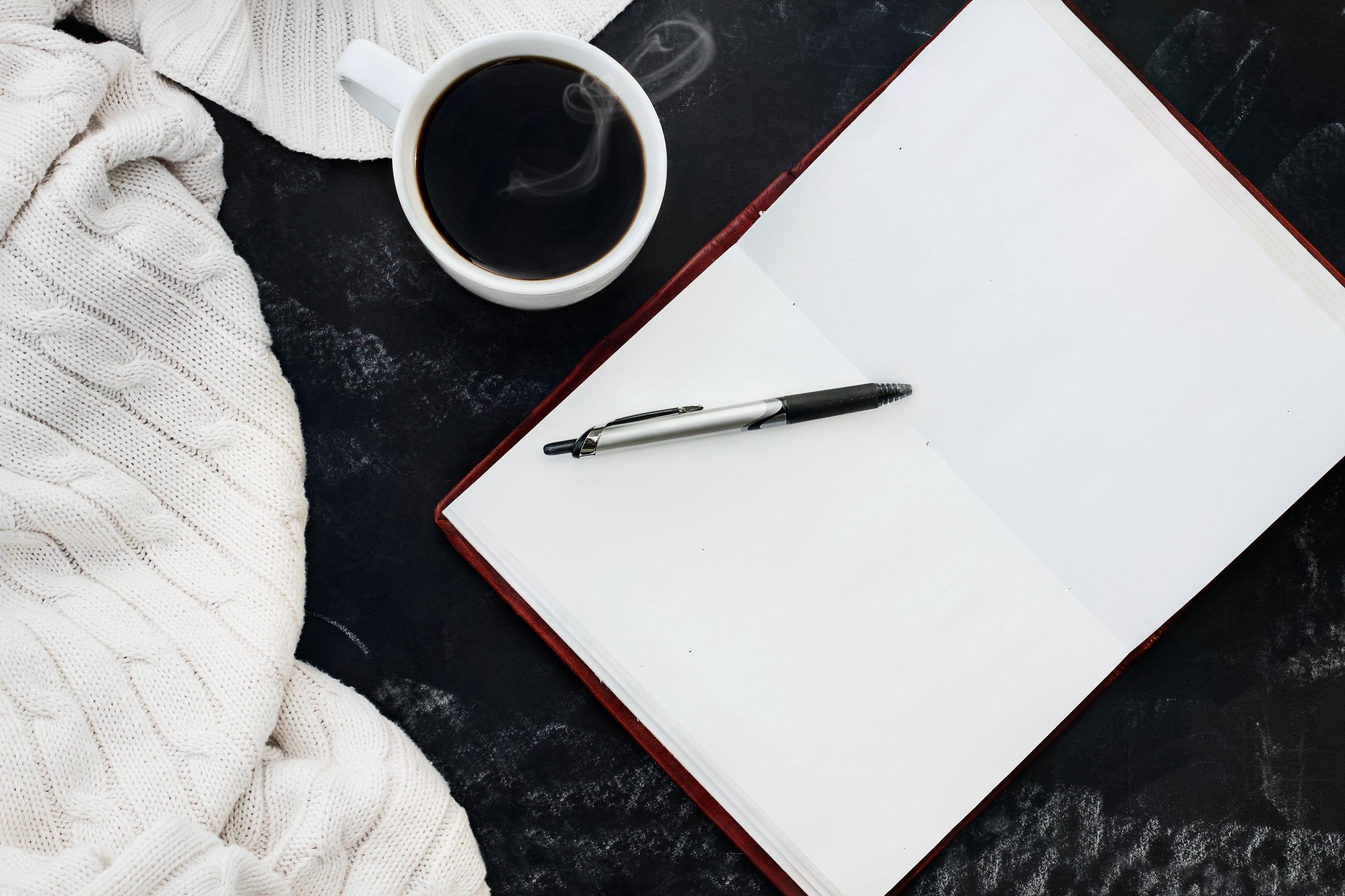 Suave manta suéter de punto con una taza de café caliente y un libro abierto con la pluma