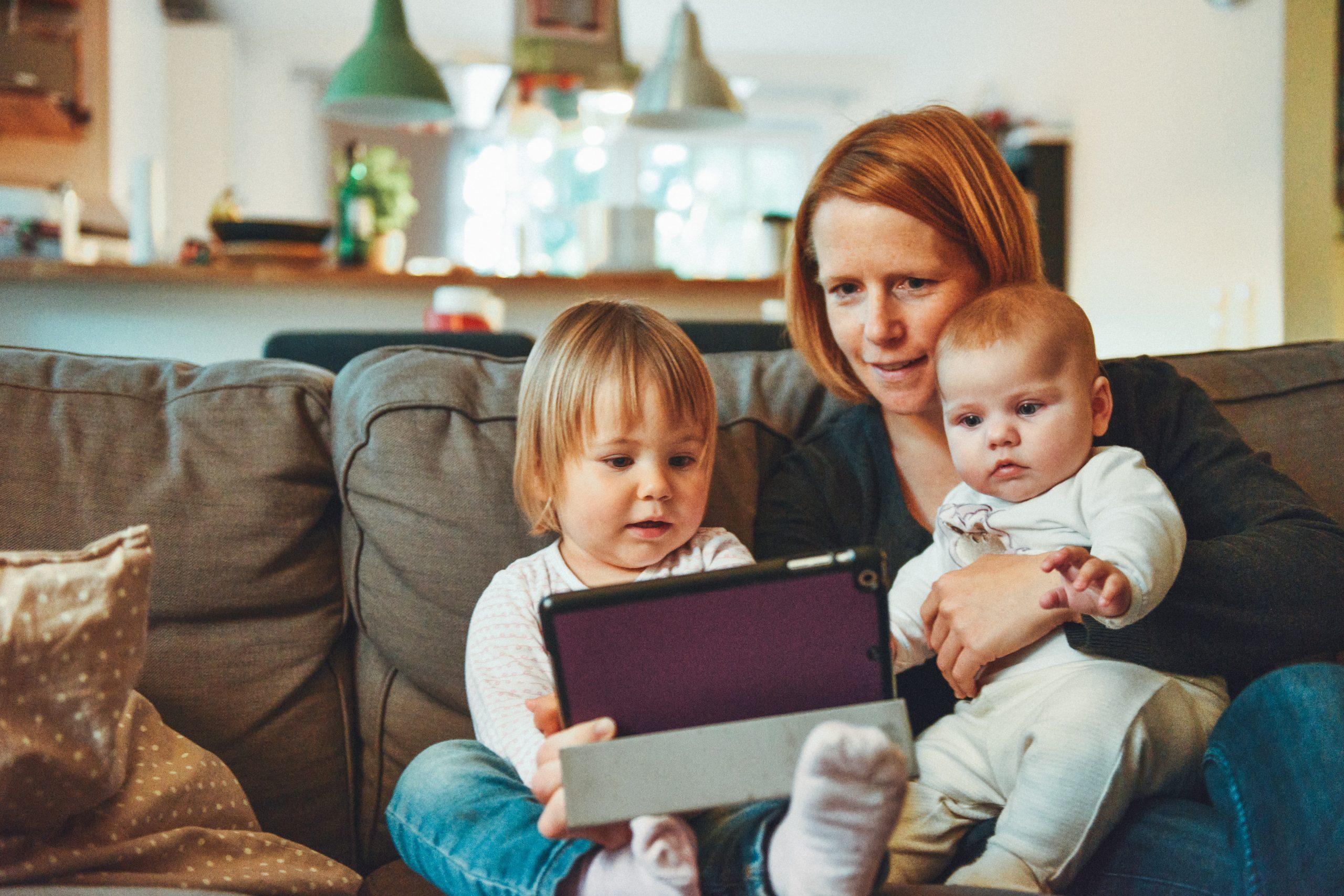 Madre con bebes en brazos jugando con tablet