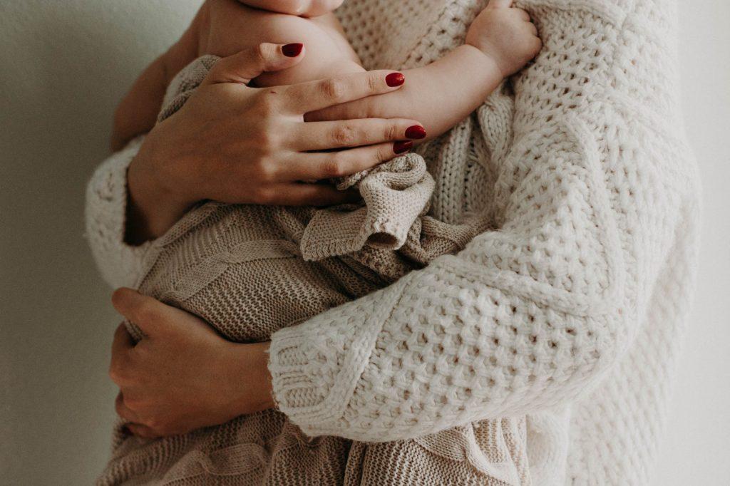 Persona sosteniendo a bebe en brazos