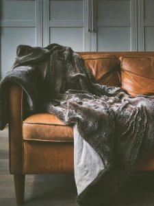 Manta de pelo gris en sofá marrón